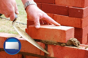 a bricklayer laying brick, building a brick wall - with South Dakota icon