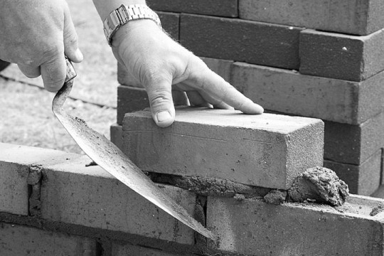 a bricklayer laying brick, building a brick wall